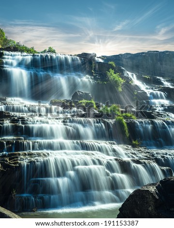 Tropical rain forest landscape with flowing blue water of Pongour waterfall at sunny day under blue sky. Da Lat, Vietnam - stock photo