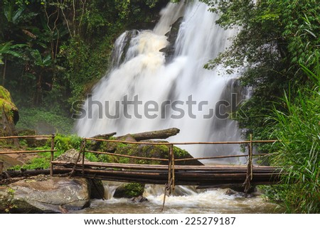 Tropical rain forest landscape with jungle plants, flowing water of Pha Dok Xu waterfall and bamboo bridge. Mae Klang Luang village, Doi Inthanon National park, Chiang Mai province, Thailand - stock photo