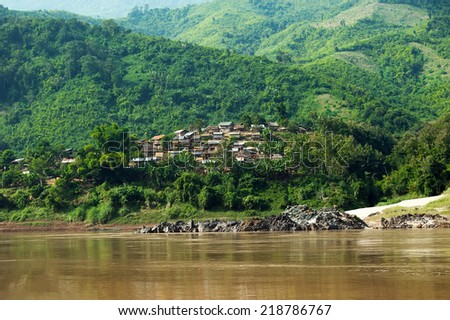 Tropical rainforest rural landscape. Small asian village with traditional wooden house in jungles along Mekong river. Laos countryside - stock photo