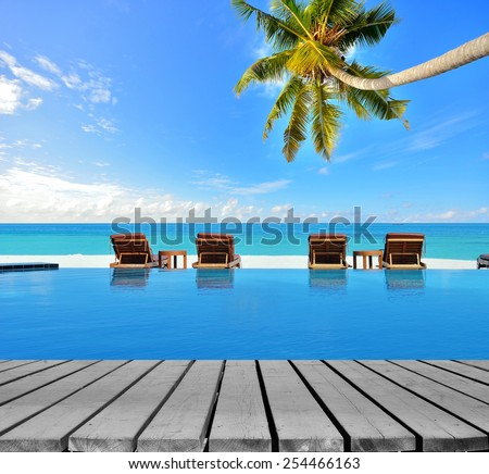 Tropical resort hotel infinity swimming pool with empty wooden platform - stock photo