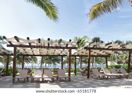 Tropical resort on empty white sand beach, ocean and palm trees in Mexico, Riviera Maya - stock photo