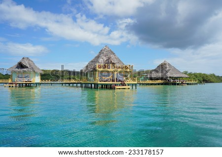 Tropical resort over water with thatched roof bungalow, Caribbean sea - stock photo