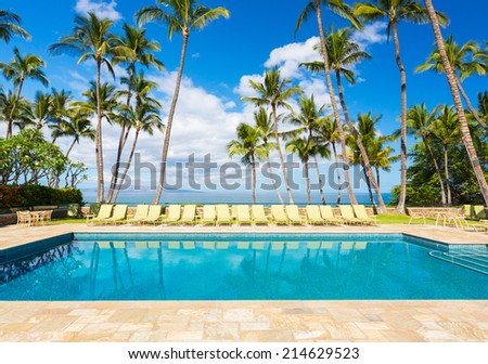 Tropical Resort Pool with Lounge Chairs, Palm Trees, and Ocean View - stock photo