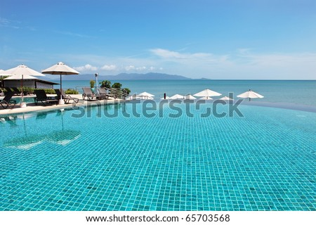 Tropical resort. Poolside with sea view - stock photo