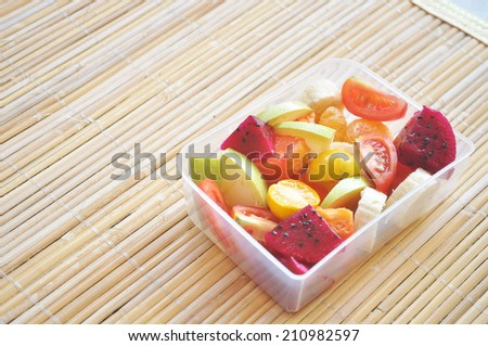 Tropical salad fruit on a plastic box and wooden tray - stock photo