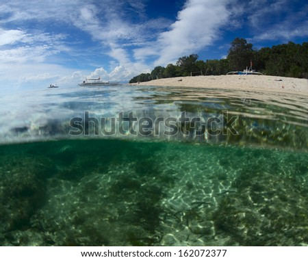 Tropical sandy beach with cloudy sky and coral reef underwater - stock photo