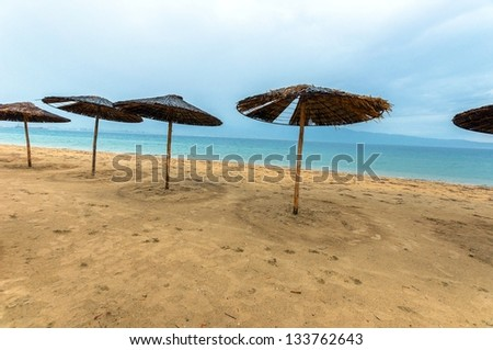 Tropical scene with Parasol and beach beds - stock photo