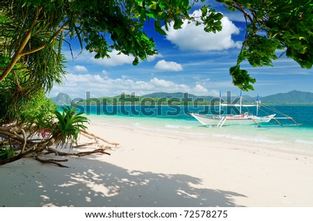 Tropical sea landscape. Boat on the beach. - stock photo