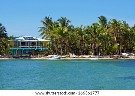 Tropical seashore with solar powered beach house and coconut trees, Caribbean, Bocas del Toro, Panama - stock photo