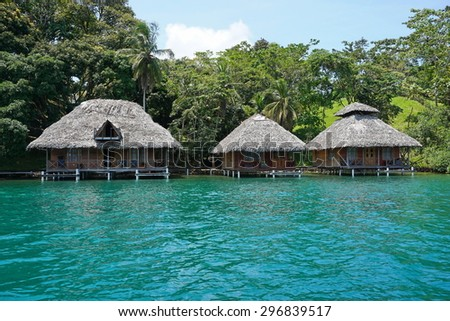 Tropical shore with thatched bungalows over the water on the Caribbean coast of Panama, Bocas del Toro, Central America - stock photo