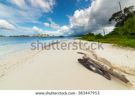 Tropical stormy weather in the remote Togean Islands, Central Sulawesi, Indonesia. From the white sandy beach to the blue lagoon, with scenic sky, islets and fishermen village in the background. - stock photo
