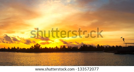 Tropical sunset and silhouette of the girl flying with umbrella - stock photo