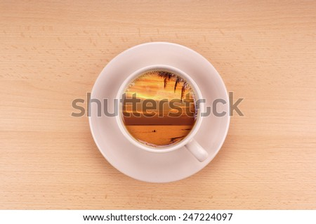 tropical sunset in a cup of coffee wanderlust concept - stock photo