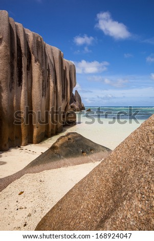 tropical trees and bushes in front of the beach with a turquoise sea, Seychelles La Digue - stock photo