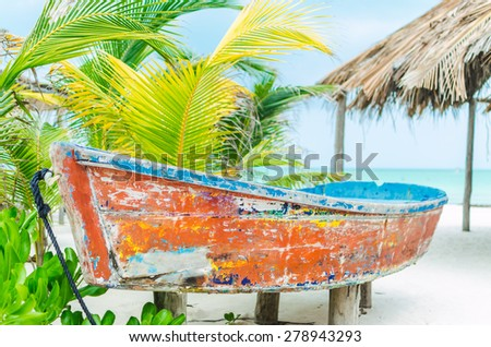 Tropical vacation beach view and tourism concept with lonely sailboat against background of turquoise sea and green palm trees on exotic white sandy beach on Holbox island, Mexico - stock photo