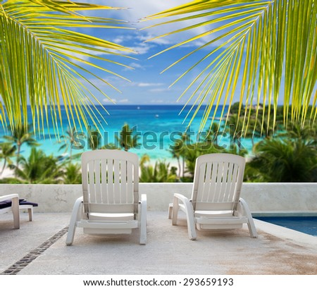 Tropical vacation. Seaview from luxury resort balcony through palm tree leafs