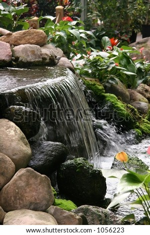 Tropical waterfall in lush greenhouse garden - stock photo