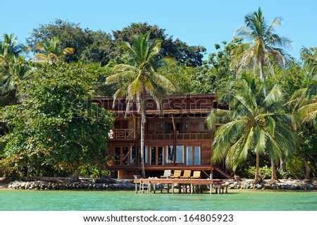 Tropical waterfront beach house with lush vegetation, Caribbean, Bocas del Toro, Panama - stock photo