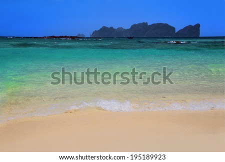 Tropical white sand beach with  turquoise water and an island on the background - stock photo