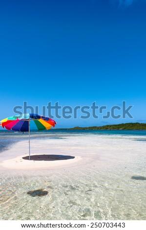 Tropical white sand island beach with umbrella and a deep blue cloudy sky - stock photo