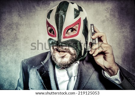 Trouble, aggressive executive suit and tie, Mexican wrestler mask - stock photo