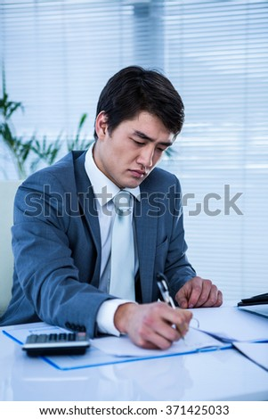 Troubled asian businessman in his desk writing somethings - stock photo