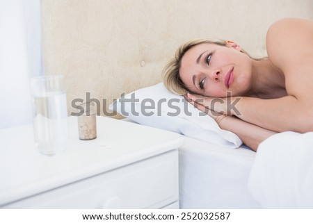 Troubled blonde looking her pills at home in the bedroom - stock photo