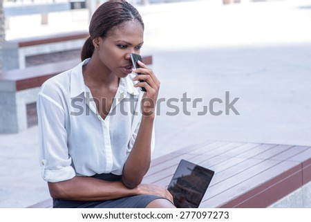 Troubled business. Confident businesswoman African businessman sitting in the street and holding cell phone in hand in Dubai downtown among the skyscrapers and looks forward - stock photo