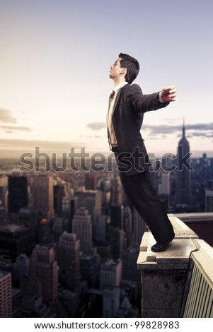 Troubled businessman letting go from the top of a building - stock photo