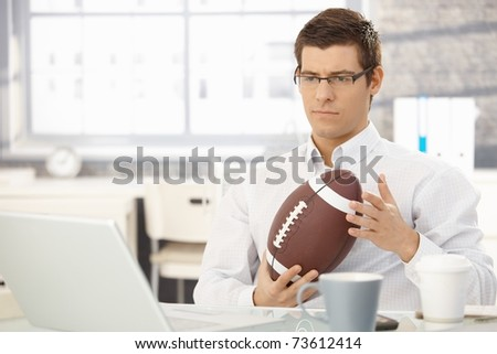 Troubled businessman thinking about work playing with football handheld in office.? - stock photo