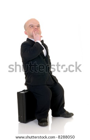 Troubled little businessman, dwarf in a formal suit with bow tie next to  suitcase, studio shot, white background - stock photo