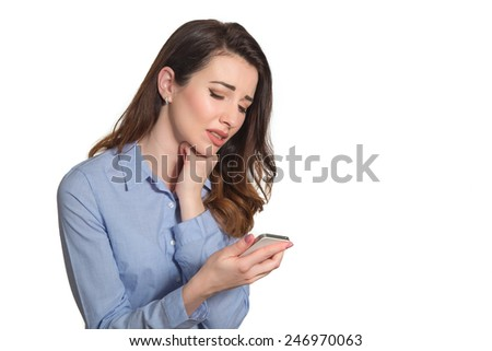 Troubled woman reading bad news text message on phone touching her head in misery isolated on white background - stock photo
