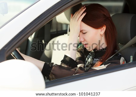 Troubles on the road, Girl hides face in hands while in a car - stock photo