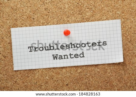 Troubleshooters Wanted typed on a piece of graph paper and pinned to a cork notice board. Business owners employ troubleshooters to look for and provide solutions to problems and improve processes - stock photo