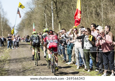 TROUEE d'ARENBERG, FRANCE- APR 12: Group of three cyclists pedaling in front excited spectators on the famous cobblestone road from the forest of Arenberg during the Paris Roubaix 2015 race.  - stock photo