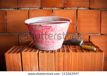 Trowel and bucket on a brick wall in a masonry workplace - stock photo