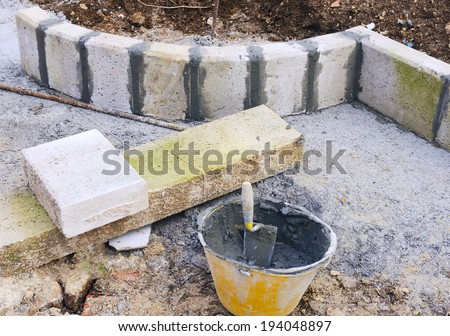 trowel  and plastic bucket on newly installed curved sidewalk curb and aligned with direction cord. - stock photo