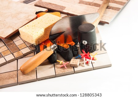 Trowel, rubber hammer, gloves, crosses and various types of tiles - stock photo