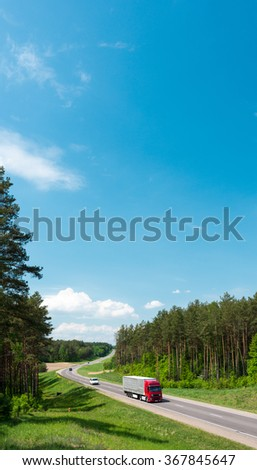 Truck and cars on country road in forest in Belarus. Blue sky with clouds in background. Beautiful and sunny summer or spring day. Road travel. - stock photo