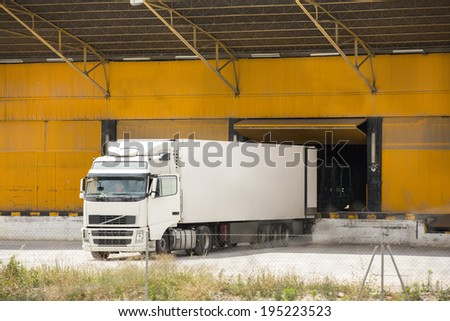 Truck at warehouse building - stock photo