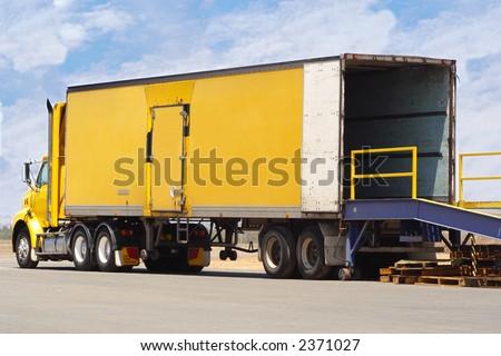 Truck backed onto loading ramp - stock photo