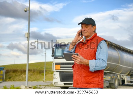 Truck driver working with tablet - stock photo