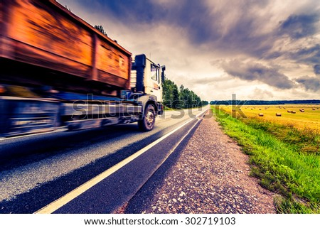 Truck driving on a rural road. View from the side of the road, image in the yellow-blue toning - stock photo