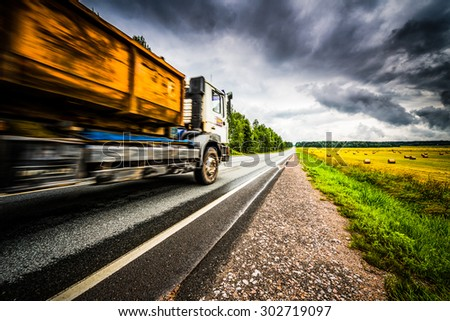 Truck driving on a rural road. View from the side of the road, image vignetting and hard tones - stock photo