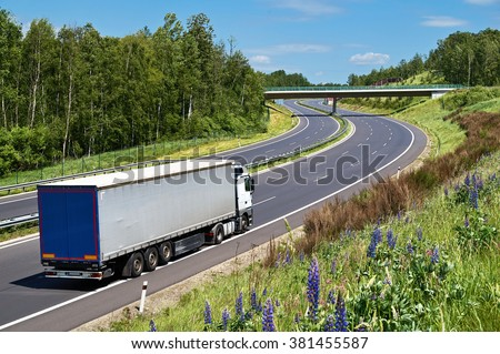 Truck driving on the highway with a double bend in a landscape. The bridge over the highway. Deciduous forest along the highway. View from above. Sunny summer day with blue skies and white clouds. - stock photo