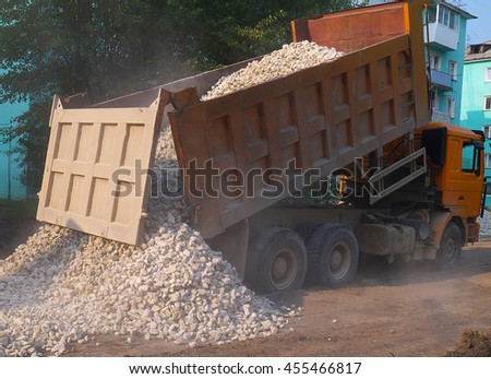 Truck dumping gravel on street roadway reconstruction site. - stock photo