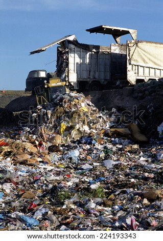 Truck dumping trash in landfill - stock photo