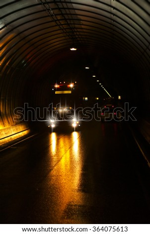 Truck in a long dark road tunnel - stock photo