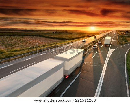 Truck in motion blur on the highway at sunset - stock photo