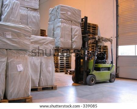 Truck lifting pallet at warehouse - stock photo